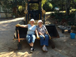 Two ladies sitting on frontend loader